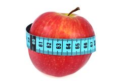 Apple surrounded by a seamstress meter on a white background. Diet concept with an apple surrounded by a flexible meter royalty free stock photography