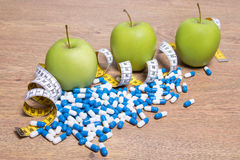 Diet concept - apples, pills and measure tape on table Stock Photo