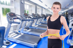 Diet concept - beautiful slim sporty woman with measure tape in Royalty Free Stock Photos
