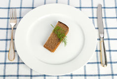 Diet concept (bread and dill on the plate). Piece of bread and dill on the plate with fork and knife on tablecloth Royalty Free Stock Photo