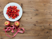 Diet concept. cherries on plate red apples and measuring tape Stock Images