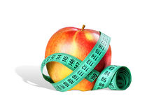 Diet concept + Clipping Path. Close-up of an apple with a measuring tape around on the white background royalty free stock photo