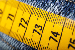 Diet concept. Close up of measure tape and jeans Royalty Free Stock Photo