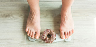 Diet Concept. Close-up of Woman`s feet On Weighing Scale With Donut. Concept of Sweets, Unhealthy Junk Food and obesity. Diet Concept. Close-up of Woman`s feet Royalty Free Stock Image