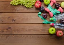 Diet concept with dumbbells measuring tape and fresh fruits Stock Image