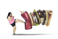 Fat woman kicking junk foods on studio. Diet concept. Fat woman kicking junk foods and a can of soda, isolated on white background Royalty Free Stock Images