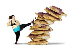 Fat woman kicking pile of pizza. Diet Concept. Fat woman kicking pile of pizza while wearing sportswear, isolated on white background Royalty Free Stock Photography