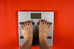 Diet concept. Female bare feet standing on scales. Top view. stock photos