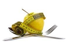 Diet concept. Fresh apple of the measuring tape. Royalty Free Stock Image
