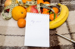 Diet concept with fruit, notebook and measuring tape Royalty Free Stock Images