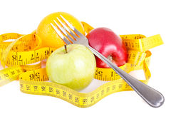 Diet concept. Fruits with measuring tape Royalty Free Stock Image