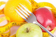 Diet concept. Fruits with measuring tape Royalty Free Stock Images
