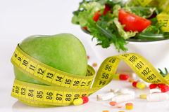 Diet concept - green apple, tablet, tape measure and lettuce Stock Image