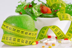 Diet concept - green apples, lettuce, pills and  measure tape Stock Images