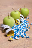 Diet concept - green apples, pills and measure tape on table Stock Images