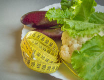 Diet concept, healthy eating, lettuce, cauliflower, eggplant, measuring tape vegetables Stock Image