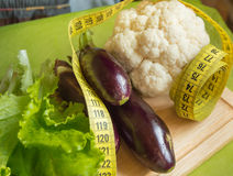 Diet concept, healthy eating, lettuce, cauliflower, eggplant, measuring tape vegetables Stock Photography