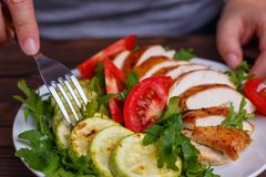 Diet concept, healthy lifestyle, low calorie food, low carb diet. Fat woman eating baked chicken breasts with zucchini and salad, close up royalty free stock photography