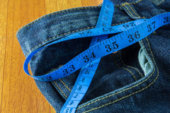 Diet concept, jeans with measure tape Stock Photos
