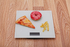 Diet. The concept of junk food on weight. Healthy Lifestyle. Wooden background. Royalty Free Stock Images