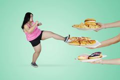Obese woman kicking unhealthy foods. Diet concept. Obese woman wearing sportswear while kicking unhealthy foods offered from someone stock photography