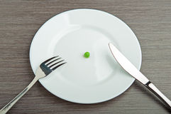 Diet concept. one pea on an empty white plate Stock Photography