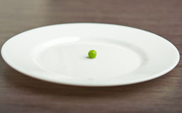 Diet concept. one  pea on an empty white plate. Diet concept. one green pea on an empty white plate Royalty Free Stock Photo