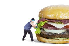 Overweight man pushing big burger. Diet concept. Overweight man wearing sportswear while pushing big burger, isolated on white background Royalty Free Stock Photo