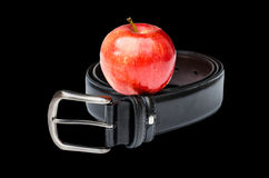 Diet concept-red apple with belt. In black background stock photo