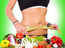 Diet concept: a slim girl measuring her weight Royalty Free Stock Photography