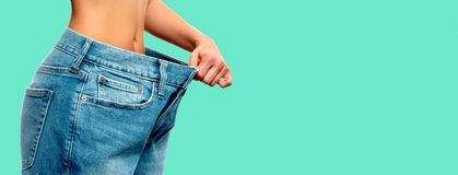 Weight loss. Woman in oversize jeans on green background. Diet concept and weight loss. Woman in oversize jeans on green background Royalty Free Stock Photo