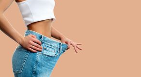 Weight loss. Woman in oversize jeans on pastel background. Diet concept and weight loss. Woman in oversize jeans on pastel background Royalty Free Stock Image