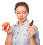 Diet concept: Woman choosing between fruits and chocolate Stock Image