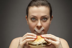 Diet concept: woman holding a burger with mouth sealed stock photo