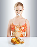 Diet concept. woman mouth sealed with duct tape with buns royalty free stock photo