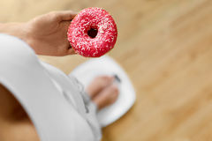 Diet Concept. Woman On Scale Holding Donut. Weight Loss. Dieting Royalty Free Stock Photo