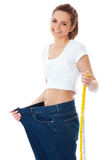 Diet concept, woman shows her old huge jeans Stock Photography
