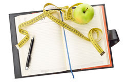 Diet diary. Notebook and pen with apple and measuring tape for writing the diet notes. Top view Royalty Free Stock Photography