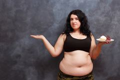 Diet, dieting concept. Beautiful young obese overweight woman wi. Th sweets, copy space stock photo