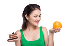 Diet. Dieting concept. Healthy Food. Beautiful Young Asian Woman. Choosing between Fruits and Sweets Royalty Free Stock Image