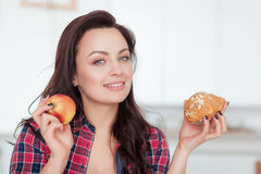 Diet. Dieting concept. Healthy Food. Beautiful Young Woman choosing between Fruits and Sweets. Weight Loss Royalty Free Stock Images
