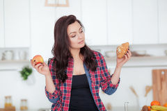Diet. Dieting concept. Healthy Food. Beautiful Young Woman choosing between Fruits and Sweets. Weight Loss Royalty Free Stock Photography