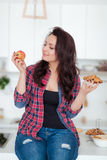 Diet. Dieting concept. Healthy Food. Beautiful Young Woman choosing between Fruits and Sweets. Weight Loss Stock Photos