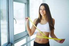 Diet. Dieting concept. Woman in Sportswear Measuring Her Waist.  Royalty Free Stock Photo