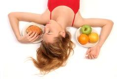 Diet dilemma. Young woman having a dilemma: greasy hamburger or fresh fruits? Heading over hamburger Royalty Free Stock Image