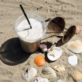 Diet drink with ice. Without calories. Ice latte on sand with cockleshells and glasses Royalty Free Stock Photos
