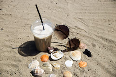 Diet drink with ice. Without calories. Ice latte on sand with cockleshells and glasses Royalty Free Stock Images