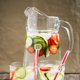 Diet drink with ice. Without calories. Water with lemon strawberries and cucumber Royalty Free Stock Image