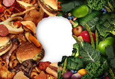 Diet Eating Choice. As a human head in a food background with half greasy junk food and the other side with green healthy fruit and vegetables as a health Stock Photos