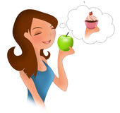 Diet eating temptation. A girl on a diet eating an apple with a temptation for a chocolate and cream cup cake Stock Photography